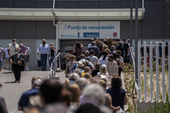 Hundreds of people queue to be vaccinated against COVID-19 at the Enfermera Isabel Zendal Hospital in Madrid, Spain, Tuesday, July 7, 2021. Spain is trying to stamp out a new wave of COVID-19 among its youth thanks to a robust vaccination program that is widely supported. Spain like the rest of the European Union got off to a slow start to compared to the United States and Britain when the first vaccines were released. (AP Photo/Olmo Calvo)