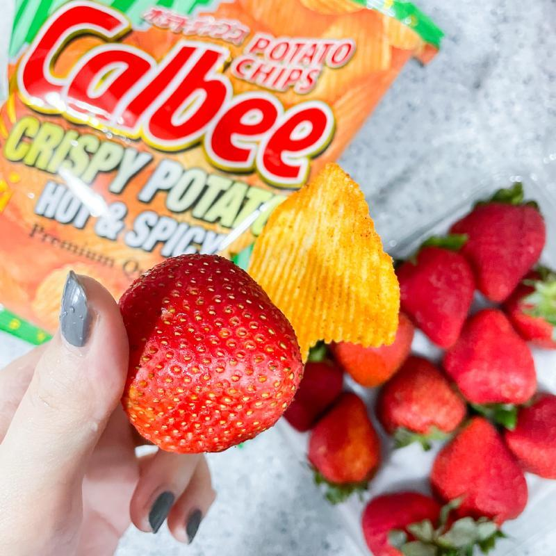 a hand in frame shot of strawberries and potato chips