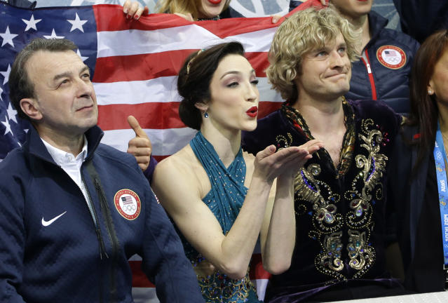 Meryl Davis, centre, blows a kiss as she and Charlie White of the United States wait in the results area after competing in the team free ice dance figure skating competition at the Iceberg Skating Palace during the 2014 Winter Olympics, Sunday, Feb. 9, 2014, in Sochi, Russia. (AP Photo/David J. Phillip )