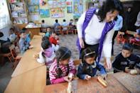 Romanian children, members of Roma community, have breakfast at the local kindergarten in Araci village, 200kms north from Bucharest, in March 2012. Continued discrimination against this minority of two million leaves the country's Roma children vulnerable. Only three percent reach high school, the education ministry said