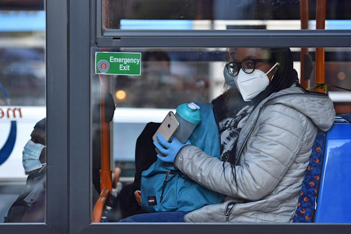 A person wearing a mask and gloves on a bus on Oxford Road in Manchester, as the Government is preparing to impose stringent new coronavirus controls on 2.8 million people after talks with the local leaders for Greater Manchester failed to reach agreement. Leaders have been given until midday on Tuesday to reach a deal, or face unilateral Government action, after 10 days of negotiations failed to reach an agreement. (Photo by Jacob King/PA Images via Getty Images)