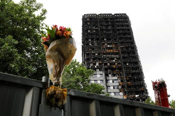 FILE PHOTO: A floral tribute is seen near the Grenfell Tower, which was destroyed in a fatal fire, in London, Britain July 15, 2017.  REUTERS/Tolga Akmen/File Photo