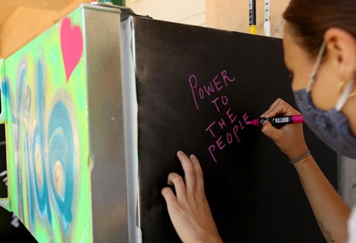 Emilia Shaffer-Del Valle writes a message on a Mid-City community refrigerator after donating food on July 12, 2020.