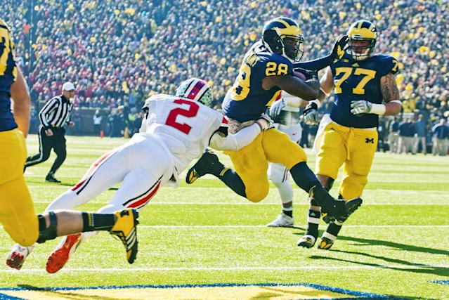 Michigan running back Fitzgerald Toussaint (28) rushes into the end zone for a touchdown as Ohio State linebacker Ryan Shazier (2) defends the first quarter of an NCAA college football game in Ann Arbor, Mich., Saturday, Nov. 30, 2013. (AP Photo/Tony Ding)