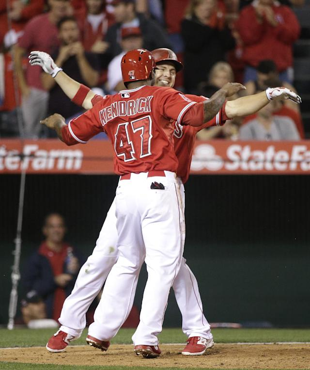 Los Angeles Angels' J.B. Shuck, facing camera, celebrates his two-run home run with Howie Kendrick during the sixth inning of a baseball game against the New York Mets on Friday, April 11, 2014, in Anaheim, Calif. (AP Photo/Jae C. Hong)