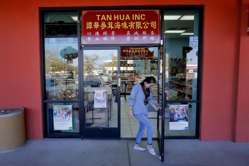 In this Feb. 13, 2020, photo, shop owner Rong Chan Tan opens her store in the Mekong Plaza in the Asian district, in Mesa, Ariz. The Asian district is trying to gain a cultural foothold in the community that previously had little Asian presence but the coronavirus outbreak in China has been impacting business in Mesa and throughout the U.S. (AP Photo/Matt York)