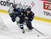 Winnipeg Jets' Kyle Connor (81) looks to pass the puck as Vancouver Canucks' Quinn Hughes (43) defends during the second period of an NHL game in Winnipeg, Manitoba, Monday, May 10, 2021. (Fred Greenslade/The Canadian Press via AP)