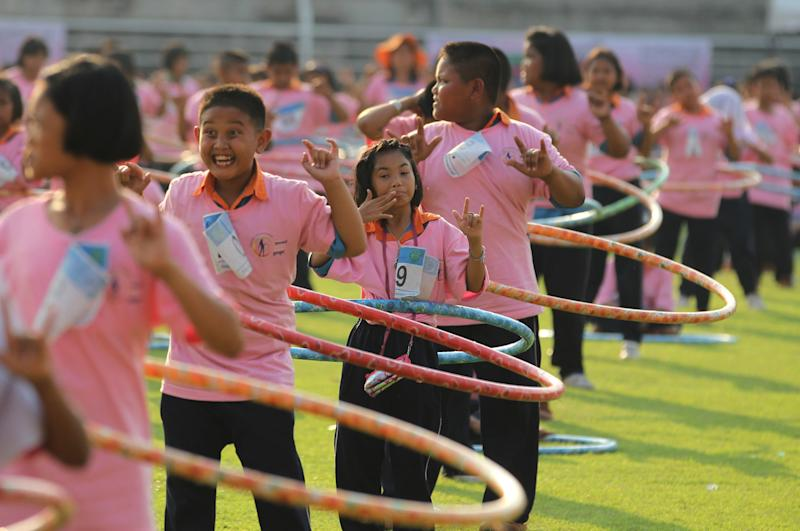 Participants perform in a hula hoop competition to break the Guinness World Record for most people dancing with hula hoops, at Thammasat University, Pathumthani, Thailand Tuesday, Feb. 12, 2013. Nearly 5,000 Thai contestants celebrated in full swing after having set a new world record for the most people dancing with hula hoops simultaneously in one place. Guinness World Records adjudicator Seyda Subasi-Gemici said Tuesday that 4,483 people had swung hula hoops to dance music for seven minutes without interruption.(AP Photo/Sakchai Lalit)