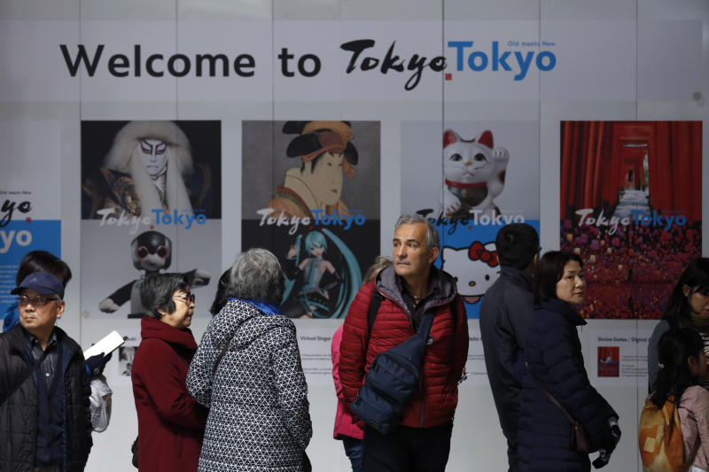 "Tourists stand in front of a ""Welcome to Tokyo"" sign while waiting in line to visit the Tokyo Metropolitan Government building's observation deck Thursday, Nov. 21, 2019, in Tokyo. The French language has been almost invisible during the drawn-out preparations for next year's Tokyo Olympics. (AP Photo/Jae C. Hong)"