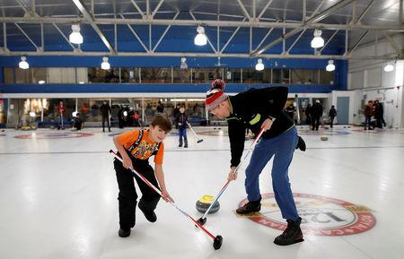 """A Yazidi refugee from Kurdistan learns curling with club member Jim Creeggan (R), at the Royal Canadian Curling Club during an event put on by the """"Together Project"""", in Toronto, March 15, 2017.    REUTERS/Mark Blinch"""
