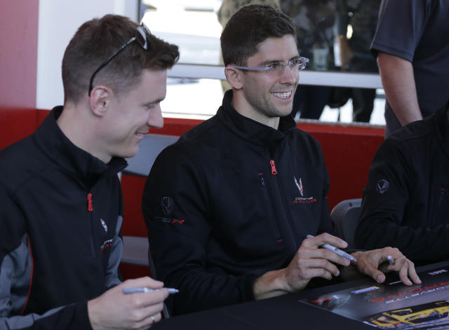 Jordan Taylor, right, driver of the Corvette Racing C8.R signs autographs as teammate Nicky Catsburg looks on before Rolex 24 hour auto race at Daytona International Speedway, Saturday, Jan. 25, 2020, in Daytona Beach, Fla. (AP Photo/Terry Renna)