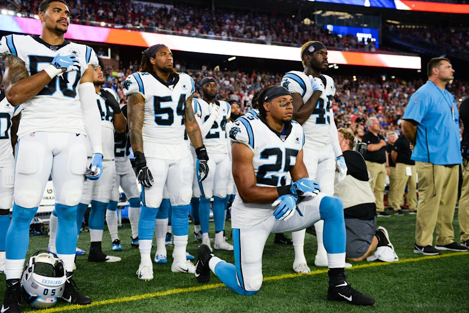 Eric Reid kneels on the sideline during the national anthem.