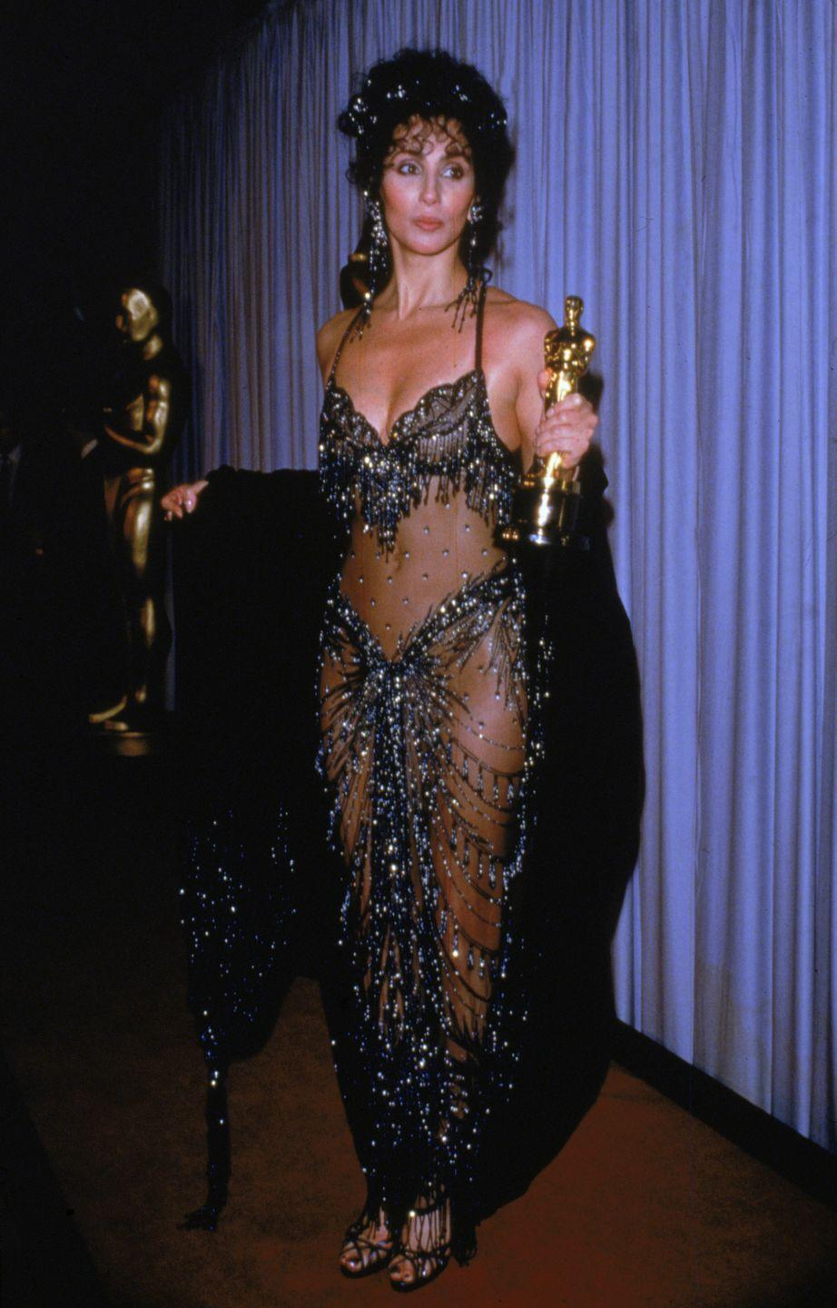 <p>In a sparkling Bob Mackie design at the Oscars winning Best Actress for her role in<em> Moonstruck.</em></p>