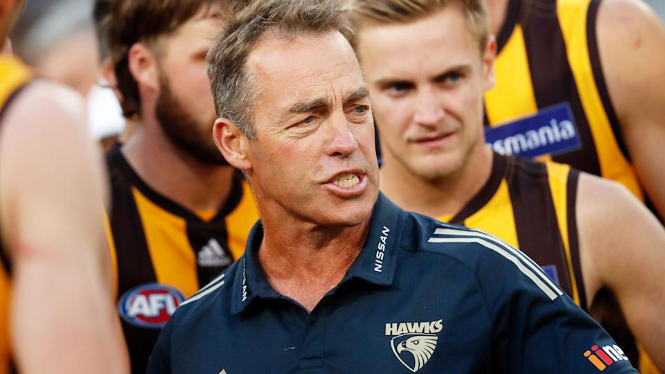Pictured here, Alastair Clarkson speaks to his Hawthorn players during an AFL game.