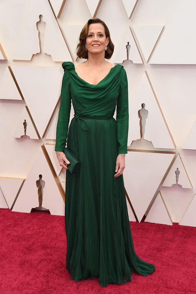 <p>In a draped green Dior Haute Couture gown. </p>
