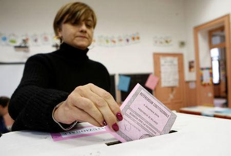 A woman casts her ballot during a referendum vote at a polling station in Milan, Italy, December 4, 2016. REUTERS/Alessandro Garofalo