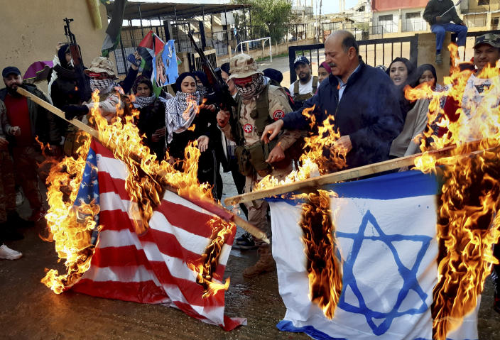 Palestinian gunmen and civilians burn the U.S. and the Israeli flags, during a protest against the White House plan for ending the Israeli-Palestinian conflict, at Ein el-Hilweh refugee camp, in the southern port city of Sidon, Lebanon, Wednesday, Jan. 29, 2020. At refugee camps across the country, Palestinians staged strikes, protests and sit-ins a day after U.S. President Donald trump revealed the long-awaited details of the plan, denouncing it as ridiculously lop-sided and saying it gives them no rights. (AP Photo/Mohammed Zaatari)