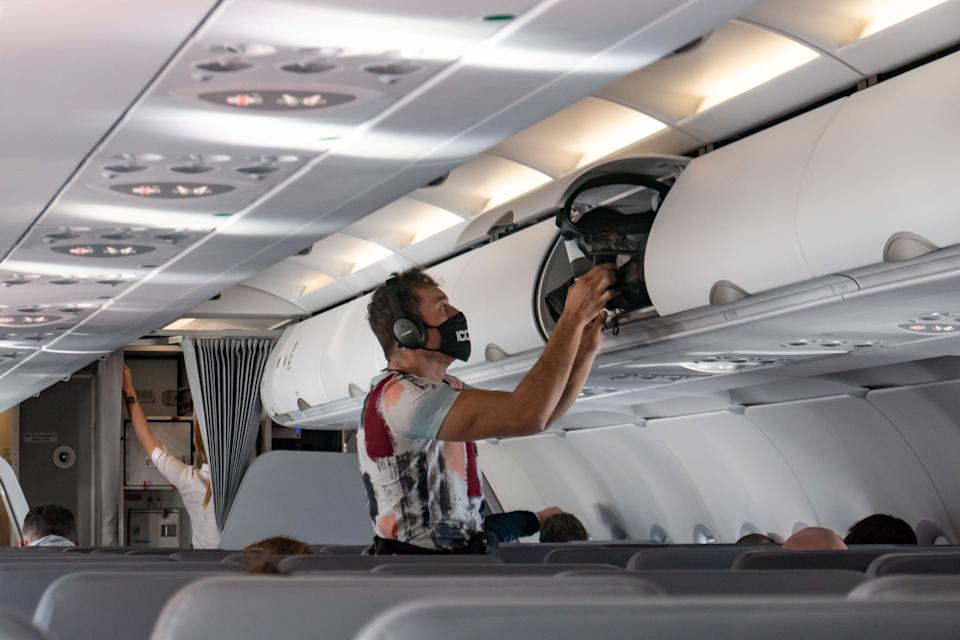 A male passenger during the flight as seen with the mandatory facemask. Flying with Lauda Airbus A320 airplane with registration 9H-LMJ during the Covid-19 Coronavirus pandemic with passenger and crew wearing facemask. Laudamotion or Lauda is an Austrian low-cost carrier owned by Ryanair and operating by Ryanair codes FR for IATA, RYR for ICAO and RYANAIR callsign. The budget airline carrier is based in Vienna International Airport  VIE LOWW or Flughafen Wien-Schwechat in Austria with a fleet of 28 Airbus Aircraft. Vienna, Austria on October 12, 2020 (Photo by Nicolas Economou/NurPhoto via Getty Images)