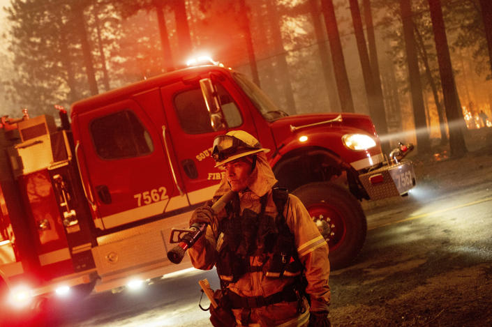 A firefighter prepares to battle the Dixie Fire, which was tearing through the Indian Falls community in Plumas County, Calif., Saturday, July 24, 2021. The fire destroyed multiple residences in the area. (AP Photo/Noah Berger)