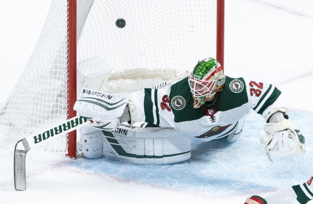 The puck goes into the net past Minnesota Wild goaltender Alex Stalock on a goal by Montreal Canadiens' Joel Armia during first-period NHL hockey game action in Montreal, Thursday, Oct. 17, 2019. (Paul Chiasson/The Canadian Press via AP)