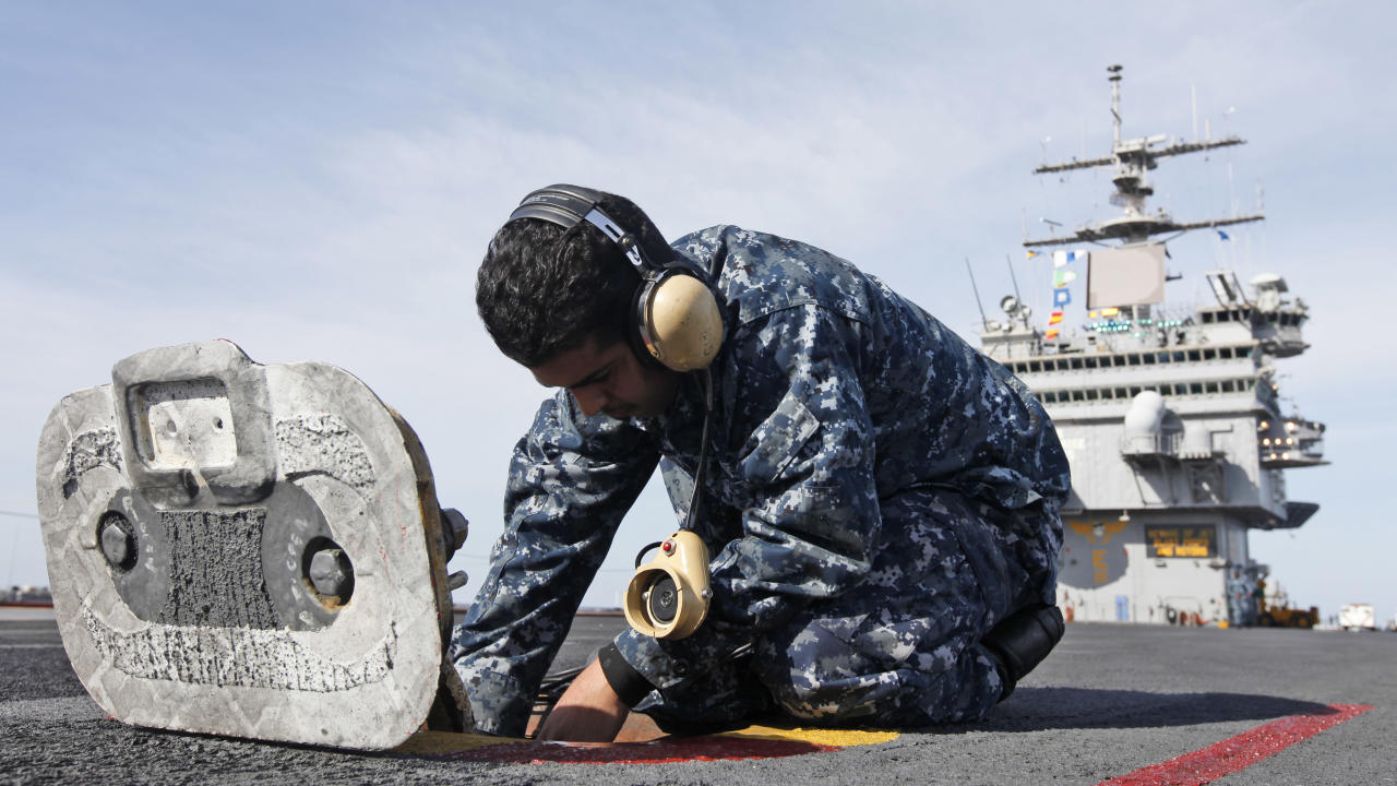 In this March 8, 2012 photo, Airman Fathi Alkaifi, from Yemen, checks communication links as they prepare for the final deployment of the nuclear aircraft carrier USS Enterprise at the Norfolk Naval Station in Norfolk, Va. The ship's storied 50-year history includes action in several wars, a prominent role in the Cuban missile crisis and serving as a spotter ship for John Glenn's orbit of the Earth. (AP Photo/Steve Helber)