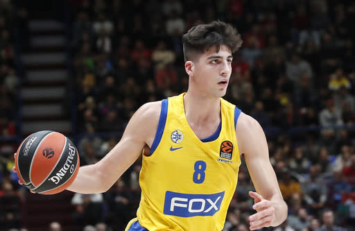 FILE - In this Nov. 19, 2019, file photo, Maccabi Fox Tel Aviv's Deni Avdija controls the ball during the Euro League basketball match between Olimpia Milan and Maccabi Fox Tel Aviv, in Milan, Italy. Avdija is a potential lottery pick and one of the top forwards in next week's NBA draft. There were 108 international players on opening-night rosters for the 2019-20 season. That number could increase this year and Avdija will be one of the new faces (AP Photo/Antonio Calanni, File)