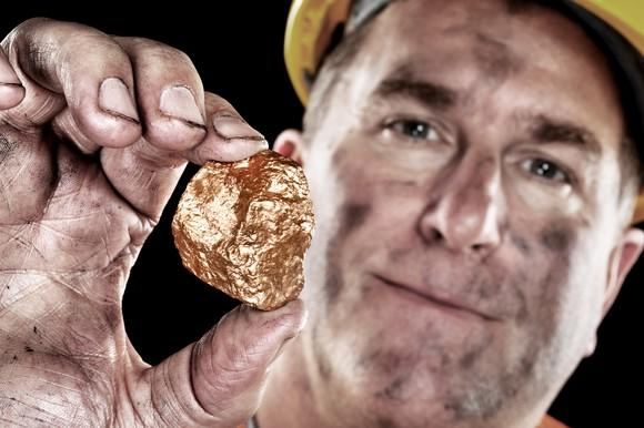 A miner holding up a gold nuggest