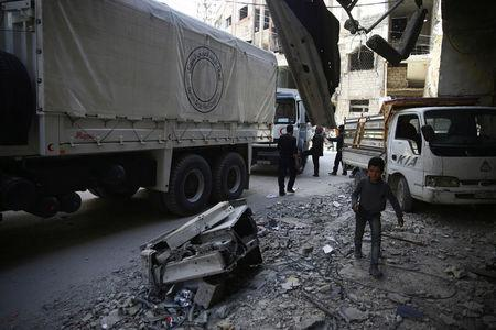 People are seen around Red Crescent aid truck in the besieged town of Douma, Eastern Ghouta, in Damascus, Syria March 9, 2018. REUTERS/ Bassam Khabieh