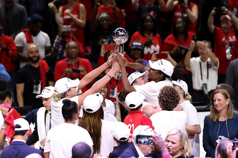 Members of the Washington Mystics celebrate after defeating the Connecticut Sun.