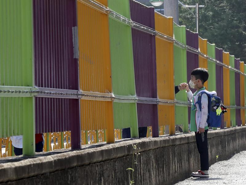 A pupil wearing a face mask to help protect against the spread of the new coronavirus holds his mother's hand through a fence as he arrives at the Ochi Elementary School in Gwangju, South Korea, Friday, May 29, 2020: AP