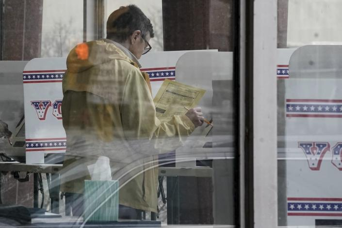 FILE - In this March 18, 2020, file photo early voters cast their ballots at the Frank P. Zeidler Municipal Building in Milwaukee, Wis. U.S. elections have been upended by the coronavirus pandemic. At least 13 states have postponed voting and more delays are possible as health officials warn that social distancing and other measures to contain the virus might be in place for weeks, if not months. (AP Photo/Morry Gash, File)