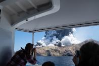 In this Dec. 9, 2019, photo provided by Michael Schade, tourists on a boat look at the eruption of the volcano on White Island, New Zealand. Unstable conditions continued to hamper rescue workers from searching for people missing and feared dead after the volcano off the New Zealand coast erupted in a towering blast of ash and scalding steam while dozens of tourists explored its moon-like surface. (Michael Schade via AP)
