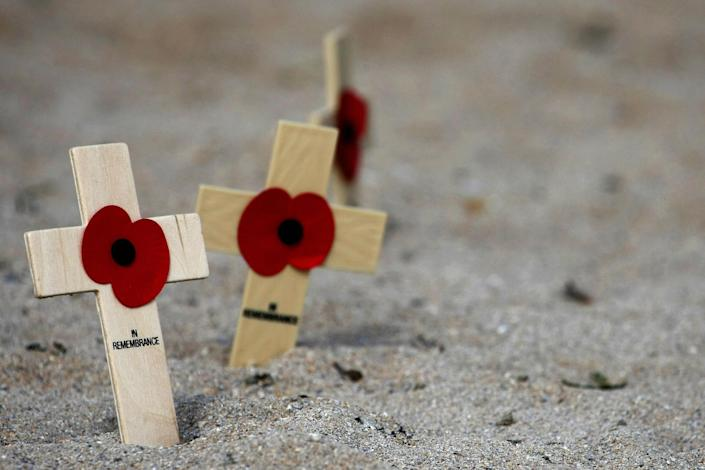 Wooden crosses with poppies are left in (Joel Saget / AFP via Getty Images file)