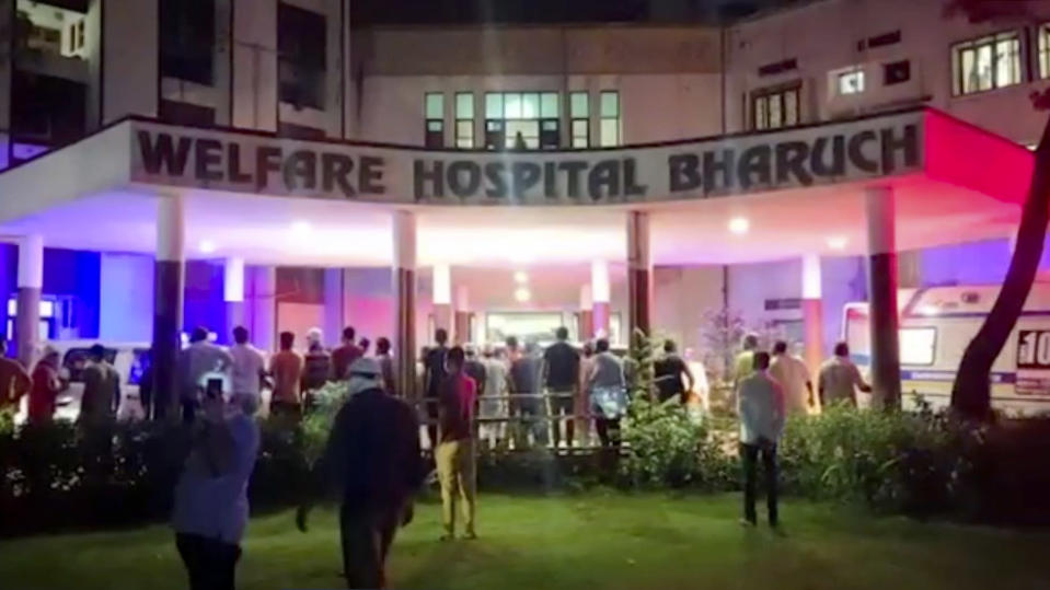 People stand around the Welfare Hospital after a deadly fire in Bharuch, western India, Saturday, May 1, 2021. The fire in a COVID-19 ward of the hospital killed multiple patients early Saturday, as the country grappling with the worst outbreak yet steps up a vaccination drive for all its adults even though some states say don't have enough jabs. (KK PRODUCTIONS via AP)