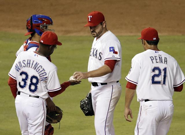 Texas Rangers manager Ron Washington (38) takes the ball from starting pitcher Joe Saunders in the fifth inning of a baseball game against the Detroit Tigers, as catcher Robinson Chirinos and Carlos Pena (21) watch, Wednesday, June 25, 2014, in Arlington, Texas. (AP Photo/Tony Gutierrez)