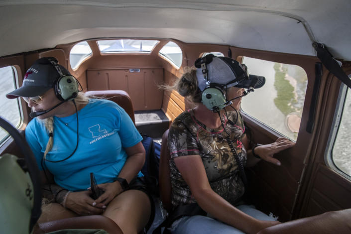 Jessica McCain, of the United Cajun Navy, and volunteer Sunshine Jacobs, of Rayne, La., help search for debris in the marsh from a seaplane as the search continues for 7 missing Seacor Power crew members, near Lake Pelto in Terrebonne Parish, La., Thursday, April 29, 2021. (Sophia Germer/The Advocate via AP)