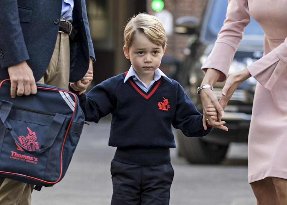 Britain's Prince George (C) accompanied by Britain's Prince William (L), Duke of Cambridge arrives for his first day of school at Thomas's school where he is met by Helen Haslem (R) head of the lower school in southwest London on September 7, 2017. / AFP PHOTO / POOL / RICHARD POHLE        (Photo credit should read RICHARD POHLE/AFP/Getty Images)