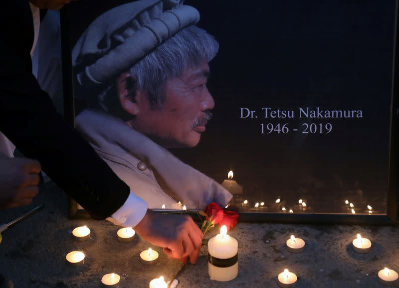 Afghan men light candles for Japanese doctor Tetsu Nakamura, who was killed in Jalalabad in yesterday's attack, in Kabul