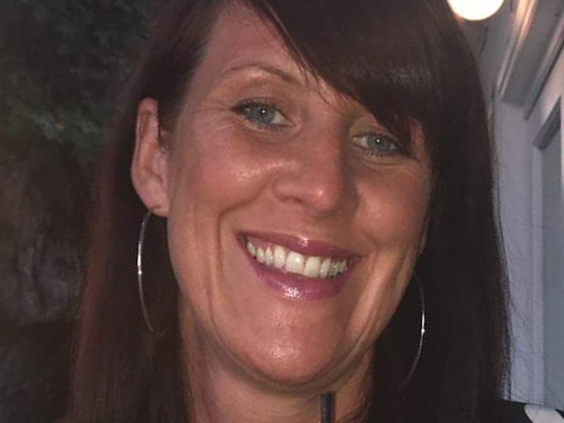 A close-up picture of Lindsay Birbeck smiling with a drink.