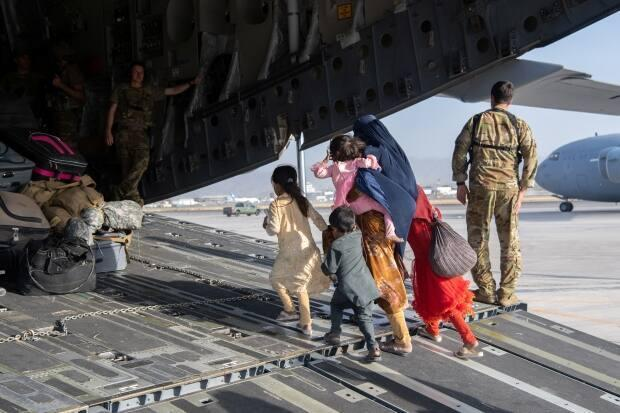 U.S. Air Force loadmasters load passengers aboard a U.S. Air Force C-17 Globemaster III in support of the Afghanistan evacuation at Hamid Karzai International Airport in Kabul, Afghanistan. (Master Sgt. Donald R. Allen/U.S. Air Force/Handout/Reuters - image credit)
