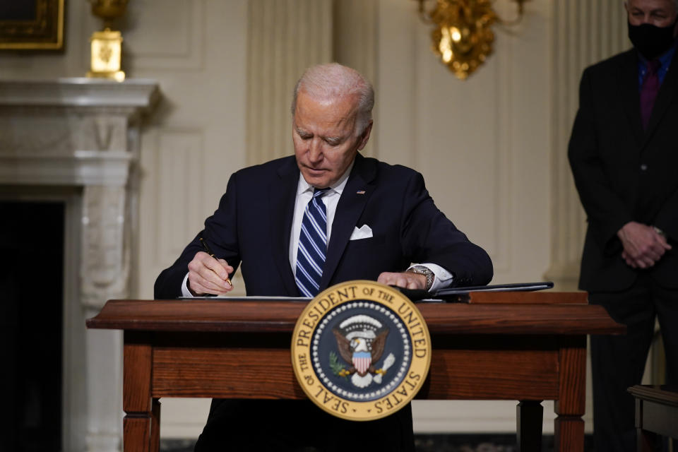 FILE - In this Jan. 27, 2021 file photo, President Joe Biden signs an executive order on climate change, in the State Dining Room of the White House in Washington. More than 300 businesses and investors are calling on the Biden administration to set an ambitious climate change goal that would cut U.S. greenhouse gas emissions by at least 50% below 2005 levels by 2030. (AP Photo/Evan Vucci)