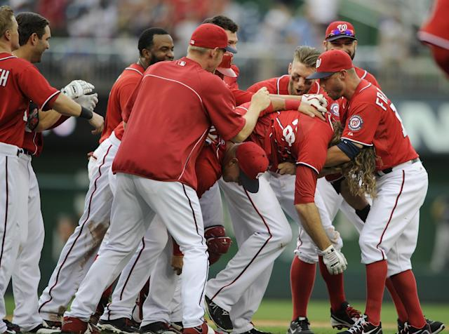 Washington Nationals' Jayson Werth, second from right, is mobbed by teammates after his walk off single drove in the winning run against the Milwaukee Brewers during the ninth inning of a baseball game, Sunday, July 20, 2014, in Washington. The Nationals won 5-4. (AP Photo/Nick Wass)