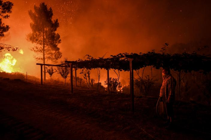 A villages holds a hose as a wildfire comes close to his house at Amendoa in Macao, central Portugal on July 21, 2019. (Photo: Patricia De Melo Moreira/AFP/Getty Images)