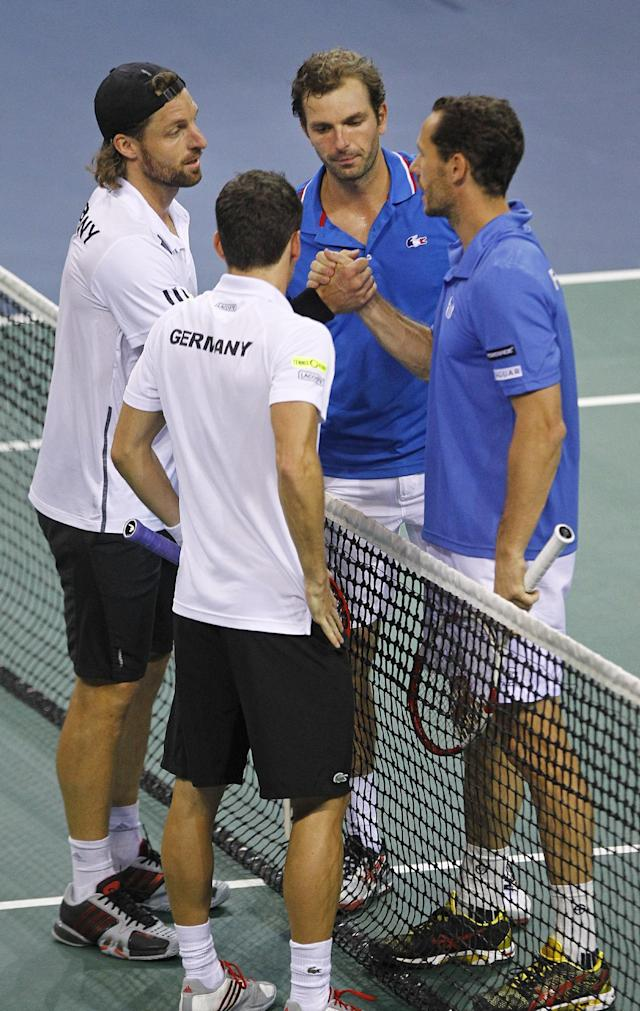 French tennis players Michael Llodra, right, and teammate Julien Benneteau, shake hands with German pair Andre Begemann, left, and Tobias Kamke, after winning their doubles match in the quarterfinal of the Davis Cup between France and Germany, in Nancy, eastern France, Saturday April 5, 2014. Germany still leads with a 2-1 score. (AP Photo/Remy de la Mauviniere)