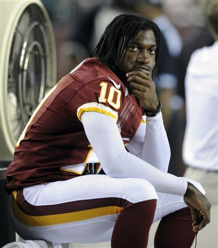 Washington Redskins quarterback Robert Griffin III sits on the bench during the first half of an NFL preseason football game with the Tampa Bay Buccaneers, Wednesday, Aug. 29, 2012, in Landover, Md. Griffin was not scheduled to play in the game. (AP Photo/Nick Wass)