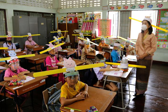 A teacher and students wearing hats designed to help them practice social distancing at a school in Thailand. (Photo: AP Photo/Wichai Taprieu)