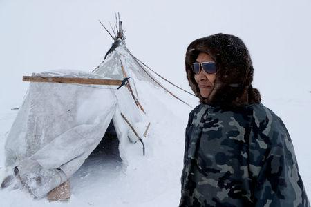 """A herder of the agricultural cooperative organisation """"Erv"""" stands in front of a traditional tent at a reindeer camping ground, about 250 km north of Naryan-Mar, in Nenets Autonomous District, Russia, March 8, 2018. REUTERS/Sergei Karpukhin"""
