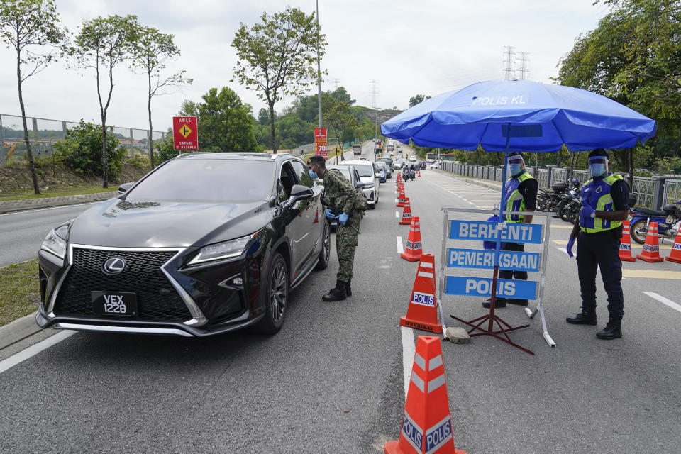 Police officers check vehicles at roadblock to ensure that people abide by the movement control order on the outskirts of Kuala Lumpur, Malaysia, Wednesday, Oct. 14, 2020. Malaysia will restrict movements in its biggest city Kuala Lumpur, neighboring Selangor state and the administrative capital of Putrajaya from Wednesday to curb a sharp rise in coronavirus cases. (AP Photo/Vincent Thian)