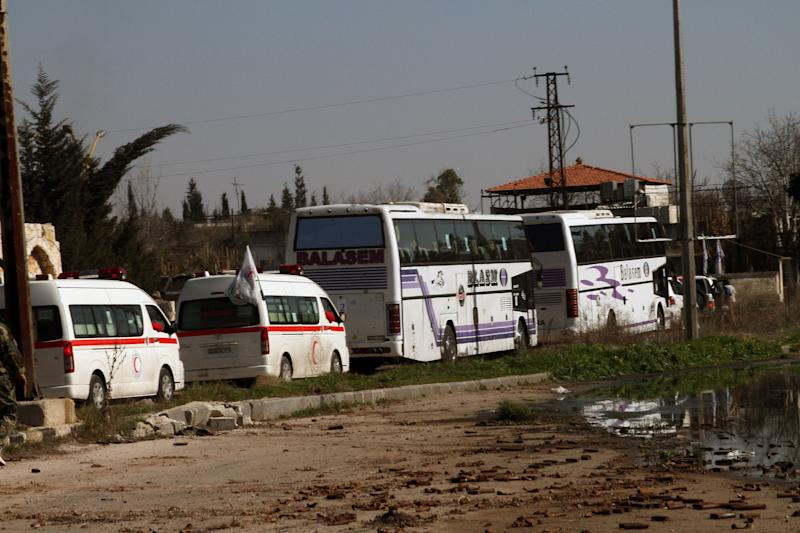 Some Syrian people on two buses followed by the Syrian Arab Red Crescent's vehicles evacuate Syria's battleground city of Homs, Friday, Feb. 7, 2014. Children, elderly women on wheelchairs and other civilians were evacuated Friday from besieged neighborhoods of Syria's battleground city of Homs under a deal struck between the government and the opposition that also included a three-day cease-fire allowing aid convoys to enter. (AP Photo)