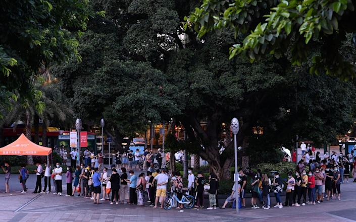People line up to test for Covid-19 at a makeshift nucleic acid testing site on Haizhu Square in Guangzhou - via Reuters